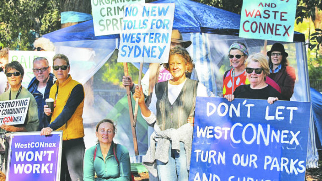 WestCONnex Action Group gathered on September 19 to support members of the group who are camping on the Euston Road side of Sydney Park to prevent the destruction of hundreds of trees and 14,000 square metres of the park that will be resumed for road widening for Westconnex. Ten days later in pouring rain #occupySydneyPark campers were huddled under tarpaulins hoping for clear weather on Saturday October 1 for the Save Sydney Park Festival. Follow developments @westconnexactiongroup. Photo: Lyn Turnbull