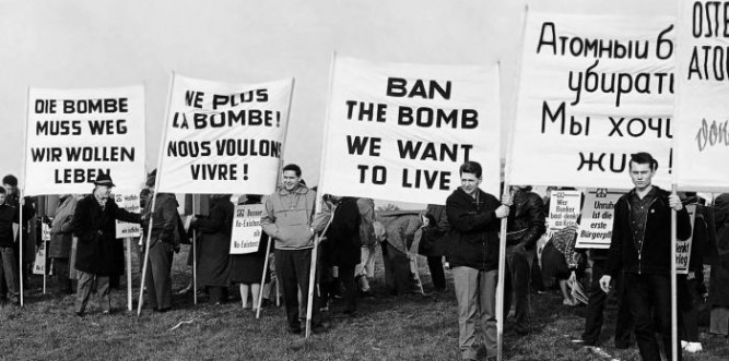 Demonstrators displaying signs in German, French, English, and Russian near a future rocket range in Bavaria, Germany, 1961. Photo: AP Photo/Lindlar