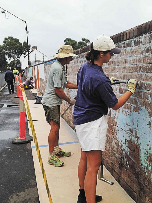 Stripping the wall for restoring the 40,000 Years mural at Redfern station Photo: Lyn Turnbull